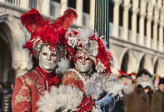 Venetian Couple. Venice, Italy- February 18th, 2012: Environmental portrait of two persons wearing nice colorful costumes and masks during the Venice Carnival Royalty Free Stock Photography