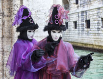 Venetian Couple. Venice, Italy- February 198th, 2012:Portrait of a couple disguised in Venetian costumes posing near a channel during the Venice Carnival days Stock Images