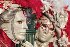 Venetian Couple. Venice, Italy- February 18th, 2012: Environmental portrait of two persons wearing nice colorful costumes and masks during the Venice Carnival Royalty Free Stock Images