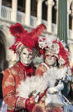Venetian Couple. Venice, Italy- February 18th, 2012: Environmental portrait of two persons wearing nice colorful costumes and masks during the Venice Carnival Stock Photo