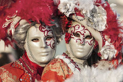 Venetian Couple. Venice, Italy- February 18th, 2012: Environmental portrait of two persons wearing nice colorful costumes and masks during the Venice Carnival Royalty Free Stock Photo