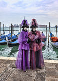 Venetian Couple. Venice, Italy- February 198th, 2012:A couple disguised in Venetian costumes pose in front of gondolas dock during the Venice Carnival days Stock Images