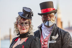 Venetian Couple. Venice, Italy- February 18th, 2012: Environmental portrait of an unidentified couple wearing black disguises and traditional Venetian masks Royalty Free Stock Photography