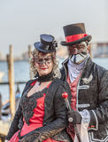 Venetian Couple. Venice, Italy- February 18th, 2012: Environmental portrait of an unidentified couple wearing black disguises and traditional Venetian masks Stock Photography