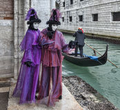 Venetian Disguise. Venice, Italy- February 18th, 2012:Two persons wearing specific costumes and masks while a gondolier is passing them on a small canal in Stock Photo