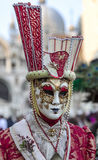 Venetian Disguise. Venice, Italy- February 18th, 2012: Environmental portrait of a person wearing a complicated costume and mask during the Venice Carnival Royalty Free Stock Photo