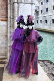 Venetian Disguise. Venice, Italy- February 18th, 2012:Two persons wearing specific costumes and masks posing near a small canal in Venice during the Carnival Royalty Free Stock Photos