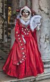 Venetian Disguise. Venice, Italy-February 18, 2012: Image of a person disguised in a beautiful red costume during the Venice carnival days stock photography