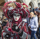 Venetian Disguise. Venice,Italy-February 18, 2012: Environmentla portrait of an unidentified person wearing a complex venetian disguise in the crowded San Marco Stock Photo