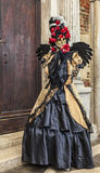Venetian Disguise. Venice,Italy- March 2, 2014: Unidentified person disguised in a black costume with a red rose posing near the walls of The Doge's Palace in Stock Photos