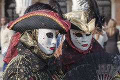 Venetian Disguises. Venice, Italy- February 18th, 2012: Environmental portrait of two persons wearing nice colorful costumes and masks during the Venice Carnival Royalty Free Stock Photography