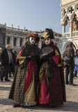 Venetian Disguises. Venice, Italy- February 18th, 2012:Two persons wearing nice colorful costumes and masks posing in San Marco Square during the Venice Carnival Stock Photos