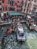 Venetian Dock. Venice, Italy-February 18, 2012: Image of tourists walking near a dock with a gondola and a transporter ship in the Rialto Bridge area in Venice Stock Photo