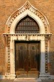 Venetian Door. Old venetian door surrounded by red terracotta tiles Royalty Free Stock Photography