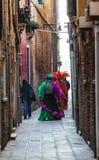 Venetian dräkter på en smal gata i Venedig Royaltyfri Fotografi