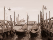 Venetian gondolas. Old-fashioned shot of venetian gondolas with a basilica in the background Stock Images