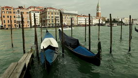 Venetian gondolas rock on the gentle waves of one of the canals on the background of beautiful architecture stock footage