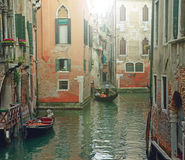 Venetian gondolier punting gondola through green canal waters of Venice Italy. Stock Photo