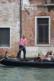 Venetian gondolier rowing through the Grand Canal, Venice, Italy Royalty Free Stock Photography