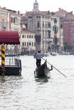 Venetian gondolier rowing through the Grand Canal, Venice, Italy Stock Photography