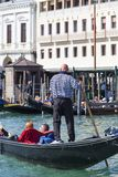 Venetian gondolier rowing through the Grand Canal, Venice, Italy Royalty Free Stock Image