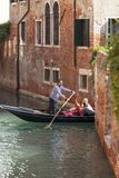 Venetian gondolier rowing through the narrow canal, Venice, Italy royalty free stock photography