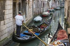 Venetian gondolier in a narrow canal of Venice, Italy stock photography