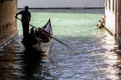 Venetian gondolier in Venice. Venetian gondolier punting gondola through green canal waters of Venice, Italy Royalty Free Stock Photos