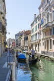 Venetian gondoliers. Venice,Italy-August 12,2014:Venetian gondoliers carry around some tourists  on a gondola in Venice During a sunny day inside her famous Stock Photography