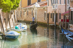 Venetian gondoliers. Venice,Italy-August 12,2014:Venetian gondoliers carry around some tourists  on a gondola in Venice During a sunny day inside her famous Stock Image