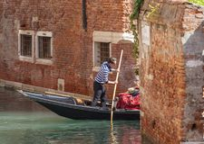 Venetian gondoljärrodd till och med den smala kanalen för sida, Venedig, Italien Royaltyfria Foton