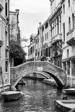 Venetian kanal med den lilla bron arkivbilder