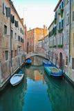 Venetian kanalgata och en bro arkivfoton