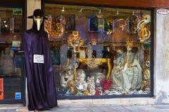 Venetian karnevalmaskering i ett shoppafönster Arkivbild