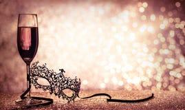 Venetian karnevalmaskering och champagne Arkivbilder