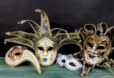 Venetian karnevalmaskeringar på grön träyttersida mot mörk bakgrund Royaltyfri Bild