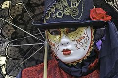 Venetian lace mask. Portrait of a beautiful woman wearing a red lace dress and white mask during the Venice carnival party in San Marco square royalty free stock photo