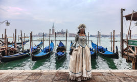 Venetian Lady. Venice, Italy- February 198th, 2012:A woman ina beautiful dress and colombina mask posing in front of gondolas dock during the Venice Carnival Royalty Free Stock Image