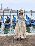 Venetian Lady. Venice, Italy- February 198th, 2012:A woman ina beautiful dress and colombina mask posing in front of gondolas dock during the Venice Carnival Royalty Free Stock Photos