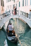 Venetian landskap med en gondol på en smal kanal Romantiskt paranseende på bron av den venetian kanalen arkivfoto