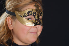 Venetian Mask. Closeup of a young blonde girl wearing a venetian mask, shot against a black background Stock Photography