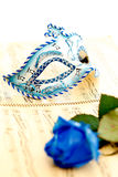 Venetian mask. Beautiful carnivale mask on a music paper, by a blue rose Royalty Free Stock Photo