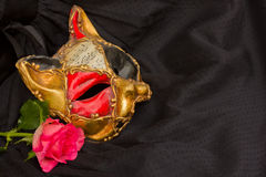 Venetian mask. Classical venetian carnival mask with rose on black silk Stock Photo