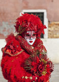 Venetian Mask. Venice, Italy- February 18th, 2012:Environmental portrait of a person in a beautiful red Venetian costume posing in Sestiere Castello during The Stock Photo