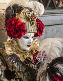 Venetian Mask. Venice, Italy- February 18th, 2012: Environmental portrait of a person wearing a Venetian mask with beautiful red roses during a the Venice royalty free stock photos