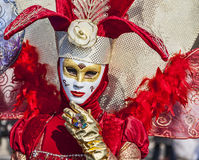 Venetian Mask Blowing a Kiss. Venice, Italy- February 18th, 2012: Environmental portrait of a person wearing a beauty red Venetian costume during a the Venice Royalty Free Stock Photography