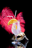 Venetian mask and cocktail. A view of a golden Venetian mask with large red feathers and a cold, refreshing cocktail in front.  Black background Royalty Free Stock Images