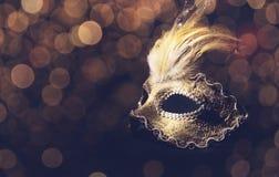 Venetian Mask. Golden venetian mask over black background stock photo