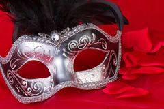 Venetian mask and hearts on red background Stock Photography