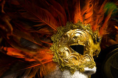 Venetian mask. An orange and red Venetian mask stock images